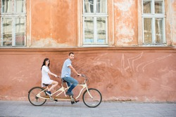 Romantic couple riding on tandem bike at the street city against the background of the old orange wall with windows. The man drives a bicycle