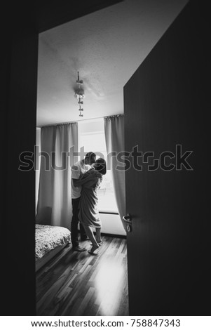 Romantic couple. Side view of beautiful young loving couple embracing and looking to each other close to window with a curtain at home. See man and woman through the small airspace from the open door.