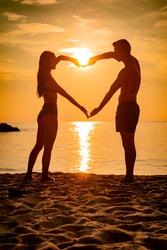romantic couple silhouette on the beach at sunrise
