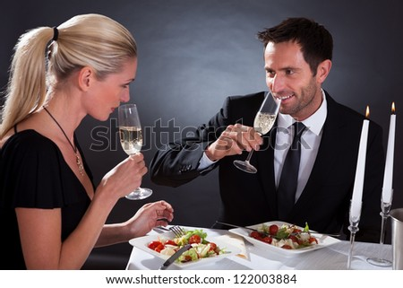 Romantic couple sitting having dinner in an elegant restaurant toasting each other with flutes of champagne