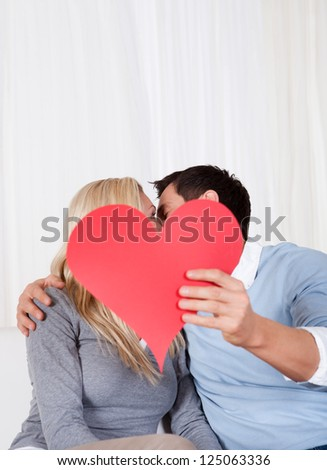 Romantic couple sitting on a sofa in a loving embrace laughing as they hold up a red paper heart for Valentines day