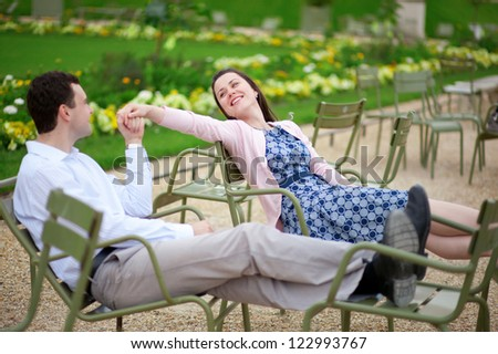 Romantic couple sitting on chairs in Luxembourg garden of Paris