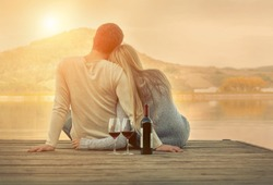 Romantic Couple sitting on the pier with red wine.