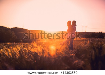 Romantic couple standing  and kissing on background summer meadow sunset #614353550