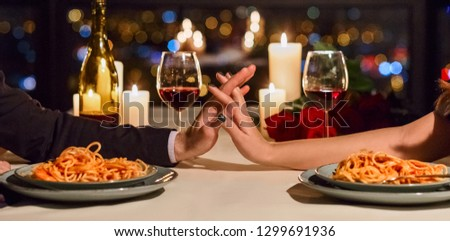 Romantic couple touching hands having dating in restaurant. Happy romantic moments together concept