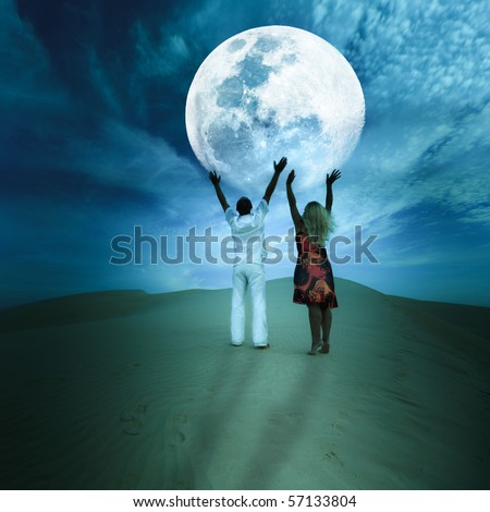 Romantic couple touching the Moon in desert