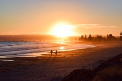 Romantic couple walking along beach at sunset, Waikanae Beach, Gisborne.