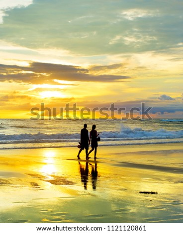 Romantic couple walking by the tropical beach at sunset. Bali island, Indonesia
