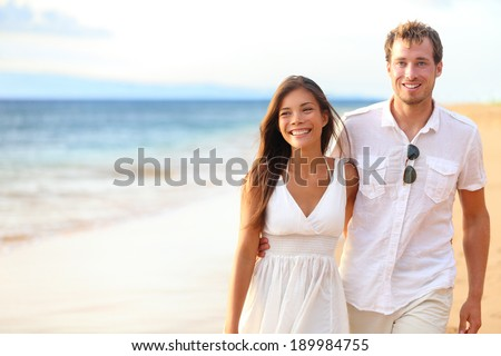 Romantic couple walking on beach on honeymoon travel vacation summer holidays romance. Young happy lovers, Asian woman and Caucasian man holding hands embracing outdoors.