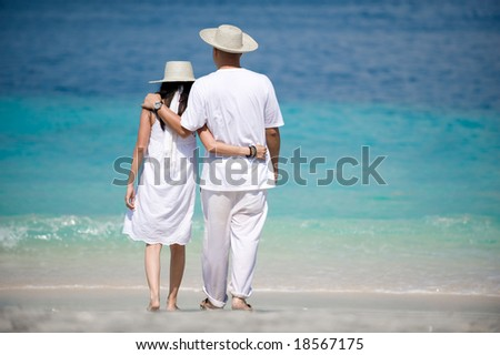 romantic couple wearing hats on the beach