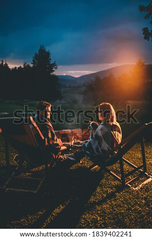 Romantic Couple With Cute Dog Relaxing In Campsite With Fire Pit. Burning Campfire with mountain landscape with night sky over the forest and hills. Getaway in wild nature.