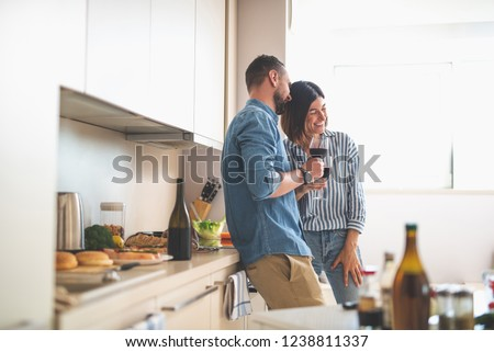 Romantic date at home. Portrait of happy bearded man and his girlfriend holding glasses of wine while talking and laughing