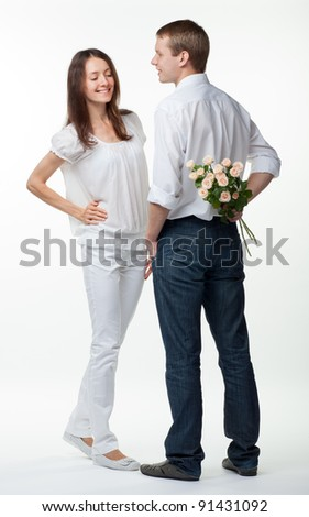 Romantic date: guy presenting flowers to young lady; isolated on white