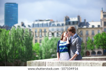 Romantic dating couple is kissing in Paris at the bridge