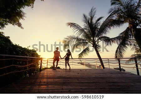 Romantic dating. Honey moon on tropical shore. Young loving couple standing together on terrace enjoying beautiful sea view. Foto stock ©
