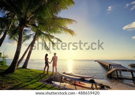 Romantic dating. Honey moon on tropical shore. Young loving couple standinng together on bay enjoying beautiful sea view. Foto stock ©