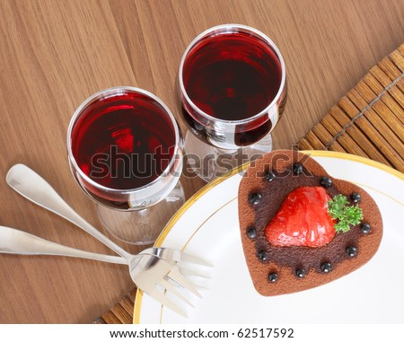 Romantic dessert. A heart shaped chocolate cake and two glasses of red wine.