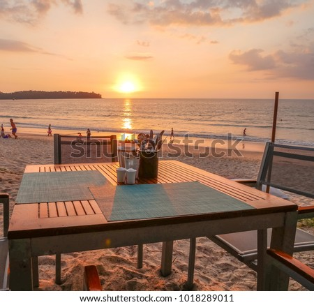 Romantic dining at cafe in nice relationship featuring silhouette by seaside over dinner on sunset having a bit of adult peaceful alone time out. On the beach during summer vacations. #1018289011
