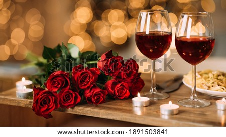 Romantic Dinner. Bouquet of flowers lying on the table, selective focus on bunch of roses, two glasses of red wine and candles on the wooden desk. Date concept, blurred background, banner, copy space