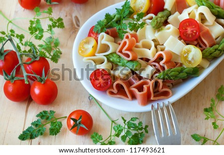 Romantic dinner. Delicious heart-shaped pasta with tomatoes, asparagus and fresh herbs - stock photo