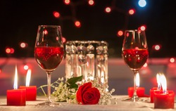 Romantic dinner. Focus on red rose.