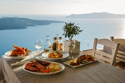 Romantic dinner for two at sunset.Greece, Santorini, restaurant on the beach, above the volcano.