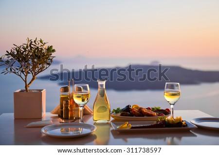 Romantic dinner for two at sunset.Greece, Santorini, restaurant on the beach, above the volcano.