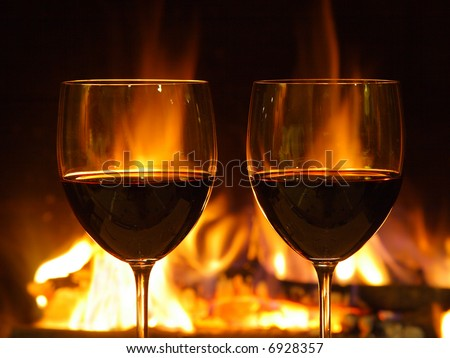 Romantic dinner for two, two glasses of red wine (close up) and fireplace.