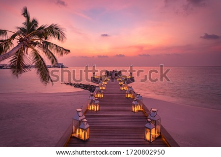 Romantic dinner on the beach with sunset, candles with palm leaves and sunset sky and sea. Amazing view, honeymoon or anniversary dinner landscape. Exotic island evening horizon, romance for a couple