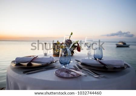 Romantic dinner setting on the beach at sunset #1032744460