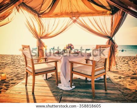 Romantic dinner setting on the beach at sunset