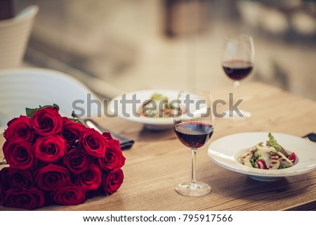 Romantic dinner settings. Two glasses of wine, dishes and bouquet of red roses are on table.
