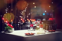 Romantic dinner setup or Holiday table setting, red decoration with candle light.