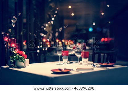 Photo of  romantic dinner setup, red decoration with candle light in a restaurant. Selective focus. Vintage color.