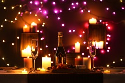 Romantic dinner table setting with burning candles and festive lights