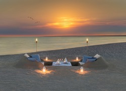 Romantic dinner with wine, candles and torches at ocean beach during wonderful sunset and flying birds couple. Honeymoon, proposal or wedding background concept.