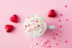 Romantic drink, coffee, latte, cappuccino with whipped cream. Top view. Pink background.