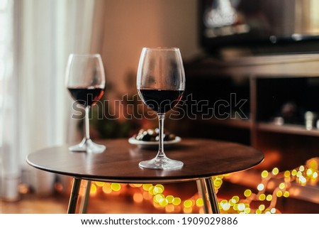 Romantic evening at home: two glasses of red wine, cosy light, tv on the background. Spending evening at home Stock fotó ©