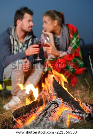 Romantic evening. Charming couple near a fire while camping drinking wine