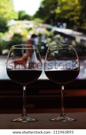 Romantic evening concept - wine and movie - lit by ambient light, and T.V. screen