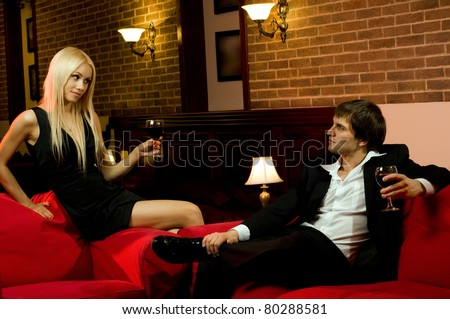 romantic evening date in hotel room,  happy couple with wine glass sit on red sofa