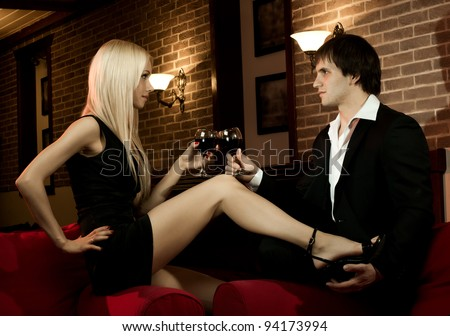 romantic evening date in hotel room,  happy couple with wine glass sit on red sofa - stock photo