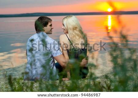 romantic evening date on nature, couple on beautiful sunset or sunrise on shore  lake
