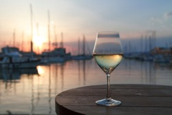 Romantic evening sunset with misty glass of white wine on background sea and yacht club.