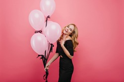 Romantic fair-haired female model celebrating birthday with charming smile. Studio shot of graceful curly girl with balloons preparing for holiday event.