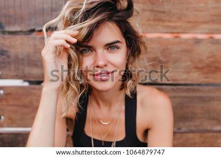 Romantic fair-haired girl chilling during outdoor photoshoot. Close-up portrait of carefree young woman with tanned skin isolated on wooden background.
