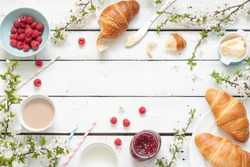 Romantic french or rural breakfast - cocoa, milk, croissants, jam, butter and raspberries on rustic white wood table from above. Countryside weekend morning concept. Background with free text space.