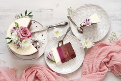 Romantic fresh flowers decorated white cake and cut pieces in plates with vintage silverware on rustic wooden background. Top view point.