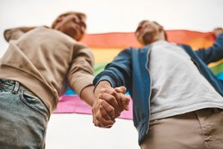 Romantic gay couple hugging, kissing and holding hands outdoors. Two handsome men holding LGBT pride flag.