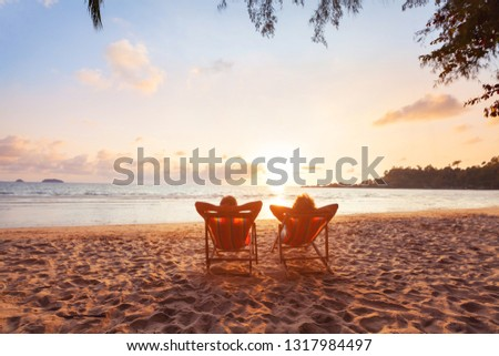 romantic getaway for couple, beach honeymoon travel, silhouettes of man and woman relaxing in hotel
